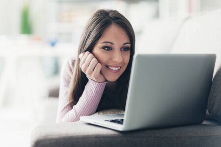 Cute girl relaxing at home, she is lying on the sofa and social networking with her laptop, communication and technology concept
