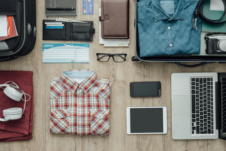 Getting ready for a trip and packing a suitcase before leaving; accessories, clothing and personal items on a desktop, travel and vacations concept 版權商用圖片