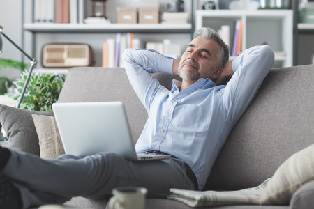 living room sofa: Happy businessman relaxing at home on the couch with a laptop on his lap, he is sleeping with hands behind head Stock Photo