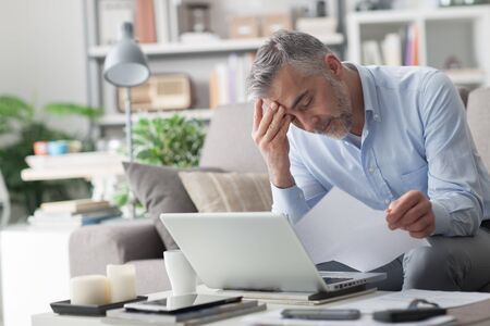 person reading: Businessman at home, he is working with a laptop, checking paperwork and bills