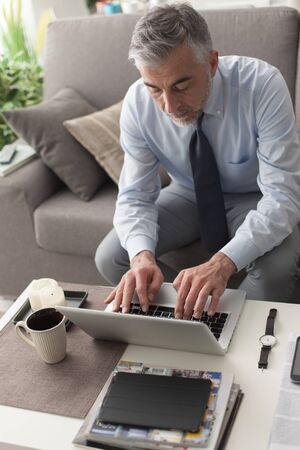 executive apartment: Businessman at home sitting on the couch and working with a laptop, business and lifestyle concept