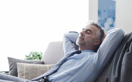 office man: Handsome businessman relaxing at home on the couch, he is sleeping with hands behind head