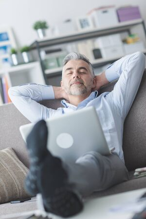 head home: Happy businessman relaxing at home on the couch with a laptop on his lap, he is sleeping with hands behind head Stock Photo