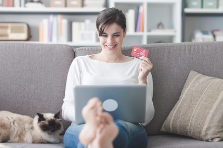 Young smiling woman at home, she is relaxing on the couch with her cat and shopping online using a credit card