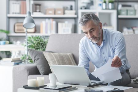 Zakenman thuis, werkt hij met een laptop, het controleren van papierwerk en rekeningen Stockfoto