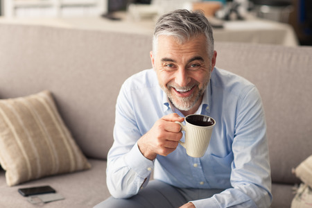 having a break: Man relaxing at home on the couch and having a coffee break, he is smiling at camera and holding a cup