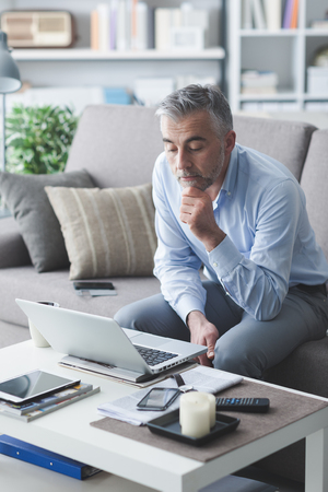 business lifestyle: Businessman at home sitting on the sofa and working with his laptop, lifestyle and business concept