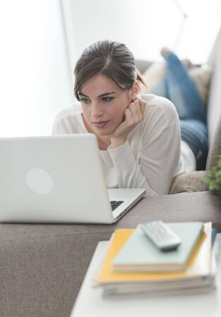 relaxing at home: Young attractive woman at home, she is relaxing on the sofa and using a laptop Stock Photo
