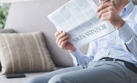 financial newspaper: Businessman sitting on the couch and reading news on the financial newspaper, unrecognizable person