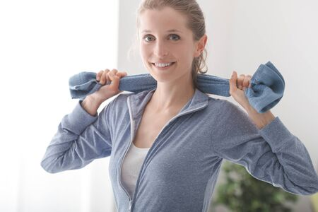 blonde woman: Confident sportswoman posing with a towel and smiling at camera, healthy lifestyle and fitness concept