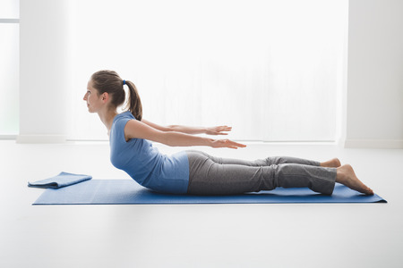 woman lying: Woman practicing yoga and meditation at home on the floor, she is holding the locust pose and bending her back Stock Photo