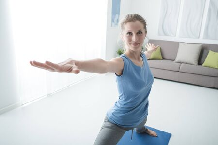 Yoga workout at home in the living room, a woman is exercising on the mat, healthy lifestyle concept