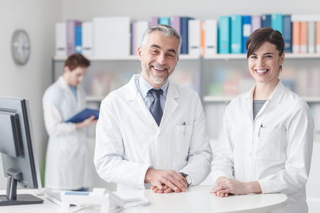 Doctor at the reception desk with his assistant, they are smiling at camera, healthcare and medical staff concept