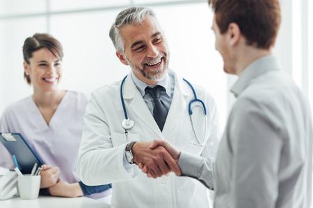 Lachende arts in de kliniek die een handdruk geeft aan zijn patiënt-, gezondheidszorg- en professionalismeconcept