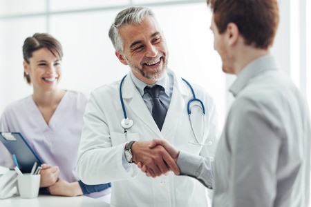 professionalism: Smiling doctor at the clinic giving an handshake to his patient, healthcare and professionalism concept