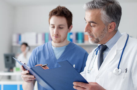 medical records: Doctor and practitioner examining patients medical records on a clipboard