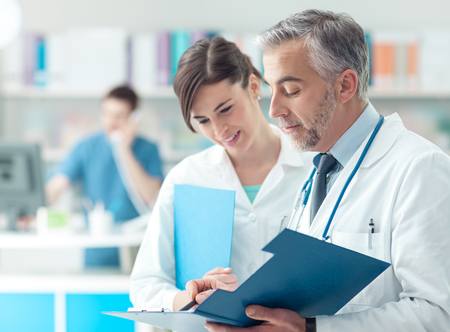 medical records: Confident doctor checking medical records on a clipboard with his female assistant, healthcare and professionalism concept