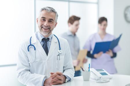 フロント デスクで自信を持って医師は、彼は両手を交差し、カメラに笑顔ポーズです。