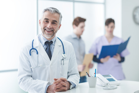 Confident doctor at the reception desk, he is posing with arms crossed and smiling at camera Stock Photo - 62025961