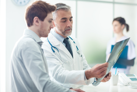 Doctor in the office examining an x-ray and discussing with a patient Stockfoto