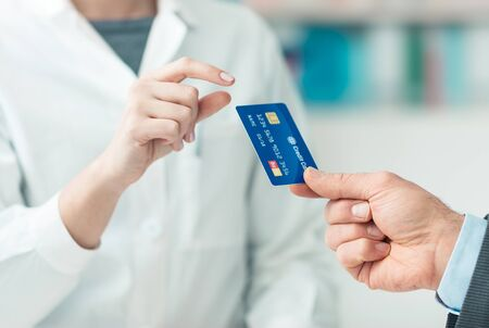 card making: Man at the pharmacy making purchases with a credit card, he is giving the card to the female pharmacist, hands close up