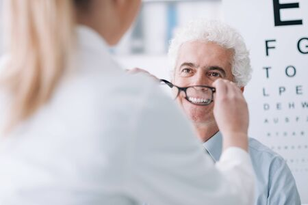 Optician giving new glasses to a male patient, he is smiling, eye chart on the background Stockfoto