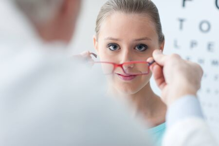 eye care: Optician giving new glasses to the patient, she is smiling and looking at camera, eye care concept