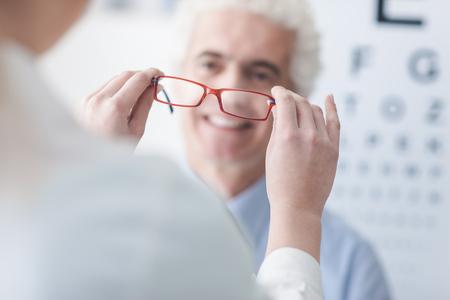 Opticien geven van een nieuwe bril aan een mannelijke patiënt, hij lacht, oog grafiek op de achtergrond