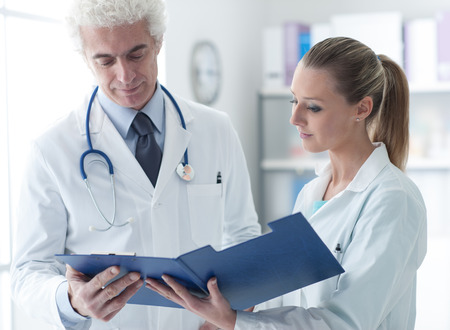 medical records: Confident doctor in the office checking medical records with his assistant, healthcare and teamwork concept