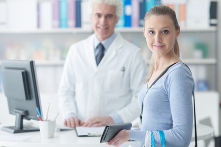doctors smiling: Patient in the doctors office, they are smiling at camera, healthcare concept