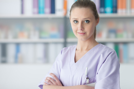 practitioner: Young female practitioner doctor posing in the office, she is smiling at camera