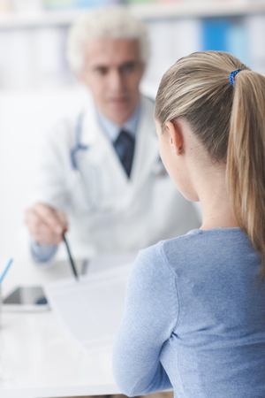 medical records: Doctor in his office showing medical records to the patient Stock Photo
