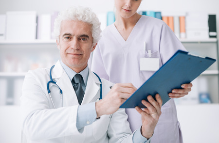 medical records: Professional doctor and his assistant working in the office, she is holding a clipboard and he is signing medical records Stock Photo