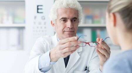 doctor giving glass: Male optometrist giving new glasses to the patient after the visit, healthcare and eye care concept