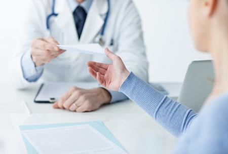 Medico nel suo ufficio dando una prescrizione medica per il paziente, concetto di assistenza sanitaria