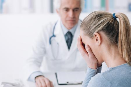 uniformes de oficina: Paciente en el consultorio del médico recibiendo malas noticias, está desesperada y llorando con la cabeza en las manos Foto de archivo