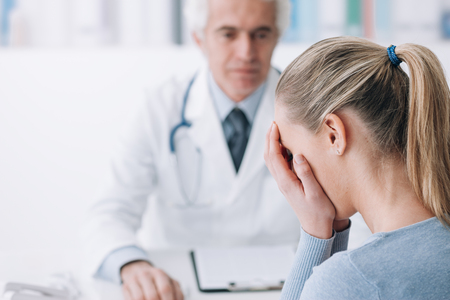 Patient in the doctor's office receiving bad news, she is desperate and crying with head in hands Stockfoto