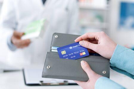 Kopen van de vrouw medicijnen en medische producten in de apotheek, is ze het nemen van de creditcard van de portefeuille Stockfoto