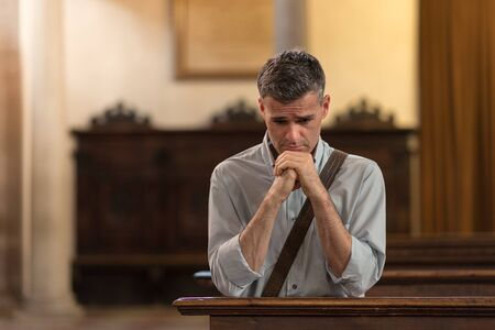 Man kneeling and praying in the Church