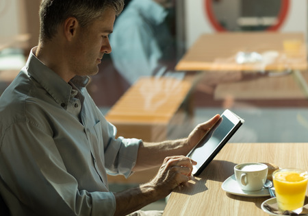 touch screen: Businessman having breakfast at the bar, he is sitting next to a window and working with a digital touch screen tablet
