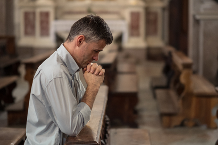 man kneeling: Religious man kneeling at the pew in the Church and praying with hands clasped Stock Photo