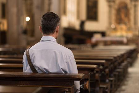 El hombre sentado en un banco en la iglesia y la meditación