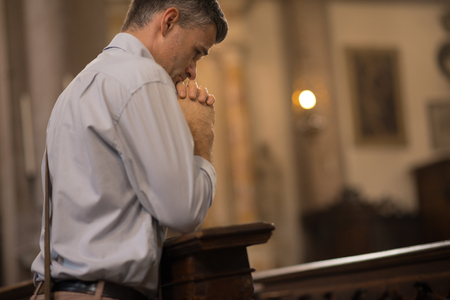 repentance: Religious man kneeling at the pew in the Church and praying with hands clasped Stock Photo