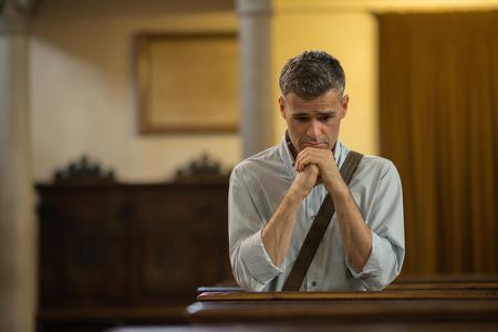 man kneeling: Man kneeling and praying in the Church