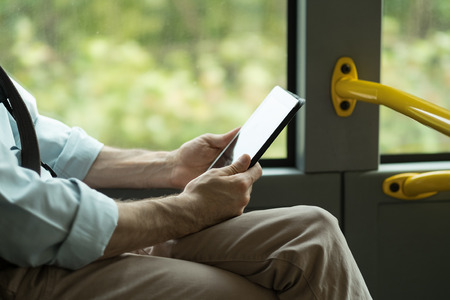 public transport: Man commuting to work by bus and working with a digital touch screen tablet, hands close up