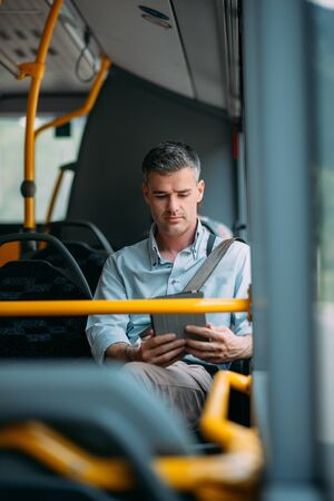 man at work: Businessman commuting to work by bus and working with a digital touch screen tablet