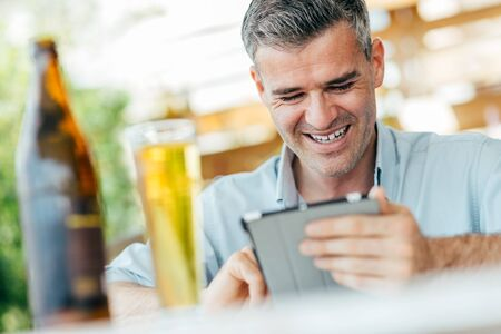 Smiling man relaxing at the bar, he is sitting at the table, having a beer and using a digital tablet Reklamní fotografie