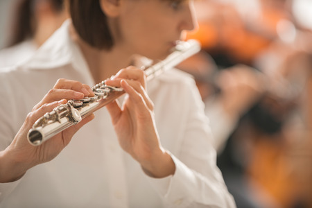 professional flute: Professional female flute player performing with classical music symphony orchestra, unrecognizable person
