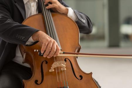 soloist: Classical music professional cello player solo performance, hands close up, unrecognizable person