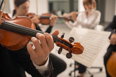 Vertrouwen violist die zijn instrument en het lezen van een muziekblad, klassieke muziek symfonisch orkest uitvoeren op de achtergrond Stockfoto